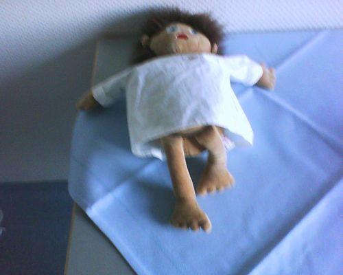 Puppe, bekleidet mit OP-Hemdchen.