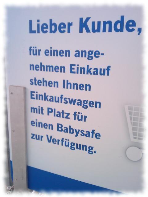 Schild: Lieber Kunde, für einen angenehmen Einkauf stehen Ihnen Einfauswagen mit Platz für einen Babysafe zur Verfügung