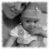 Aurela mit Mama und Infusionskanüle am Kopf.