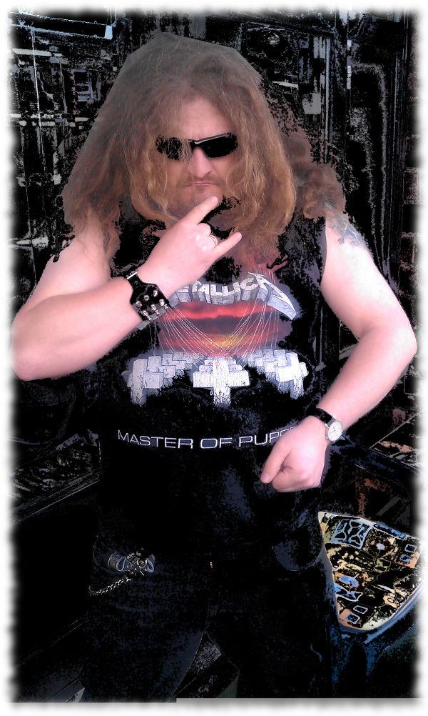 Ich posierend als böser Metalhead, Pommesgabel, offene lange Haare, Metallica-T-Shirt, Sonnenbrille, grimmiger Blick.