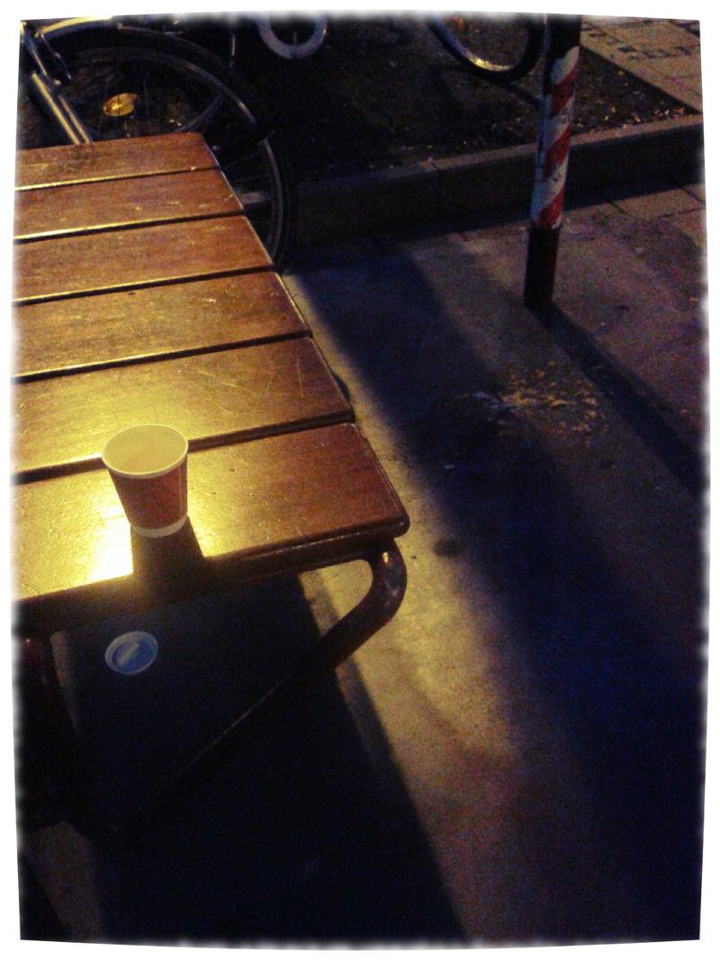 Bushaltestelle im dunklen. Auf der Sitzbank ein Pappbecher für Kaffee, auf dem Pflaster Kotze.