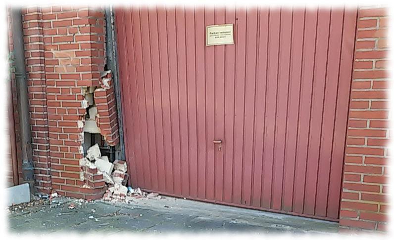 Beschädigtes Garagentor samt beschädigter Wand.