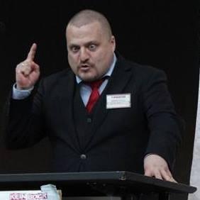 Im Anzug, mit erhobenem Zeigefinger und schielend eine Rede haltend.