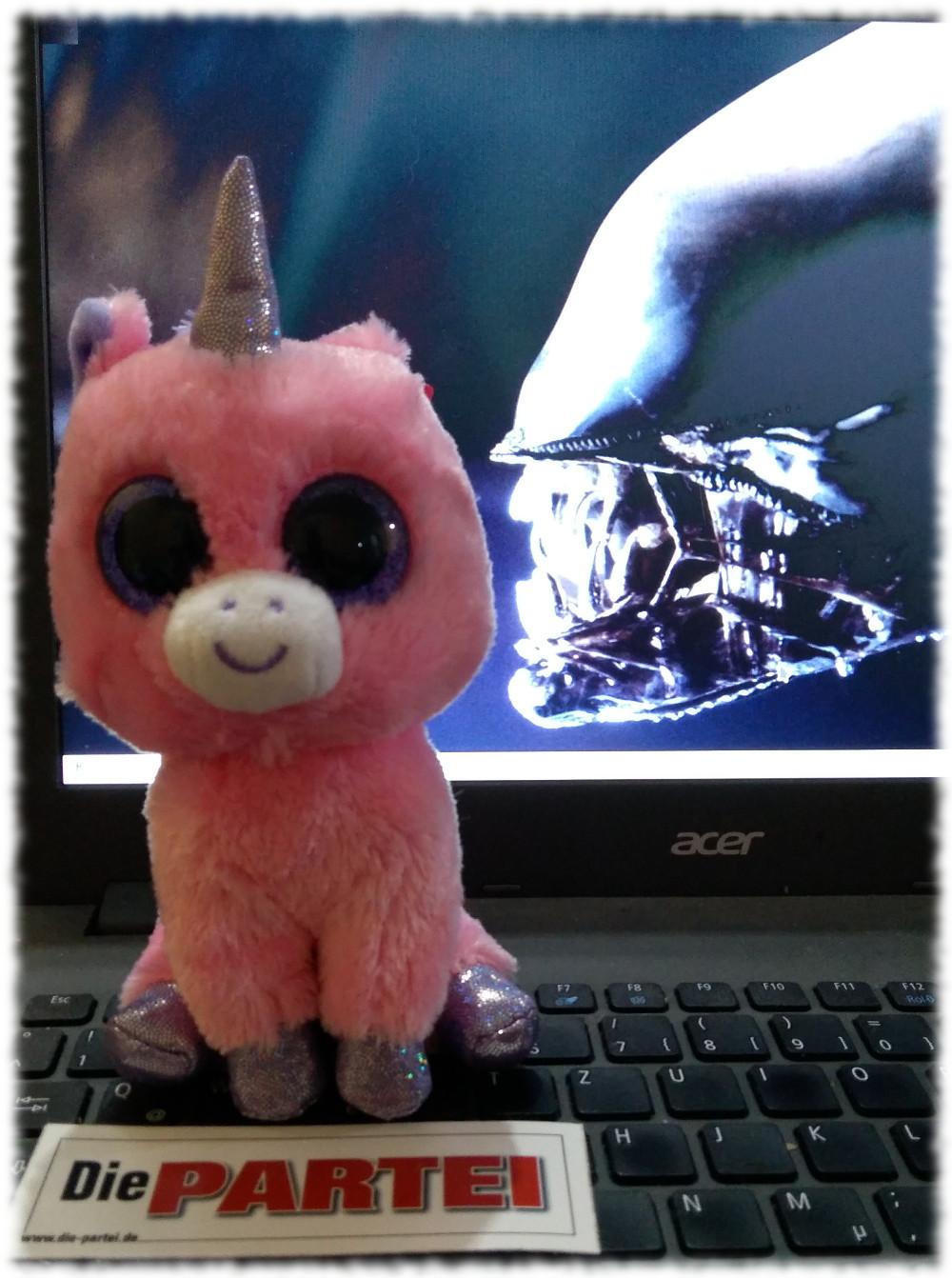 Rosa Plüsch-Babyeinhorn auf Notebook, im Hintergrund Desktop mit im Zuschnappen begriffenem Alien.