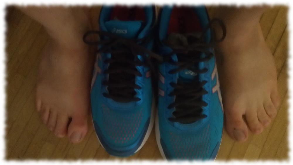 Ein Paar Laufschuhe, umrahmt von einem Paar nackter Füße.