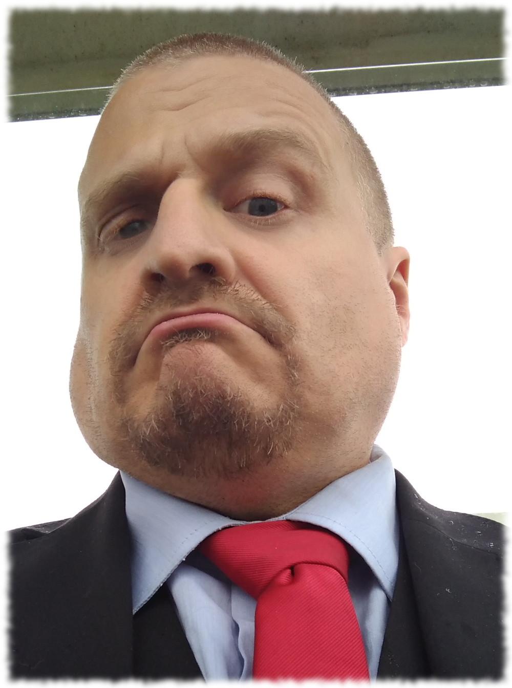 Im Anzug, blauem Hemd und roter Krawatte im Propagandaeinsatz für Die PARTEI.