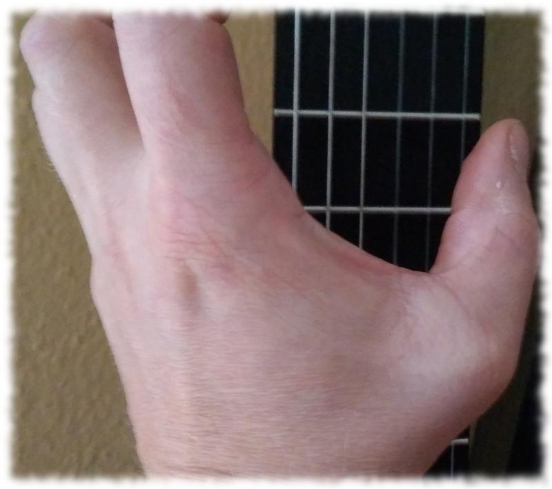 Linke Hand beziehungsweise Daumen vor Gitarrengriffbrett.