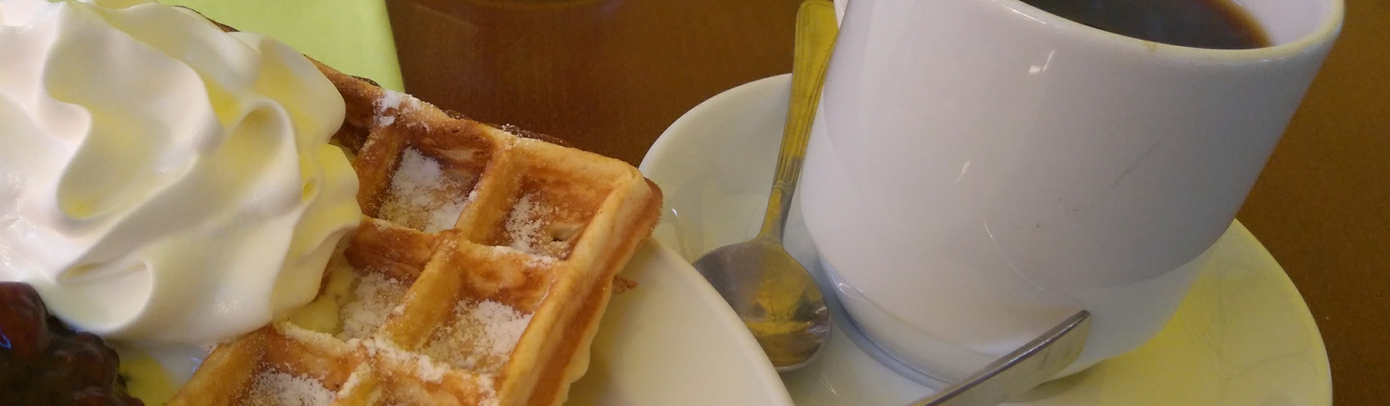 Marktfrühstück aus Kaffee und Waffel mit Sahne und heißen Kirschen