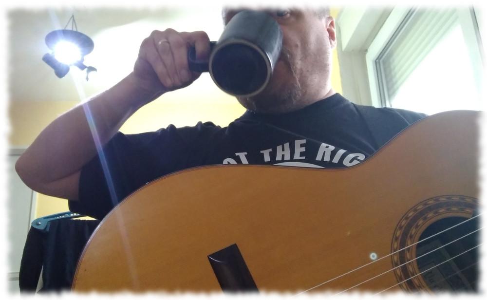 Ulf trinkt Tee mit Gitarre auf dem Schoß.