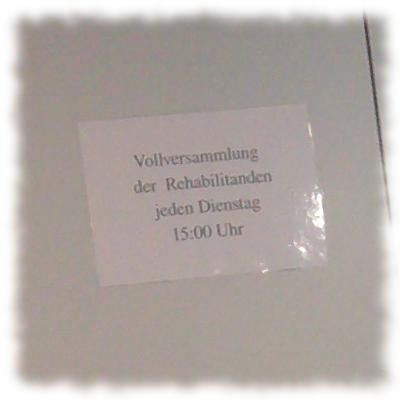 Schild: Vollversammlung der Rehabilitanden jeden Dienstag um 15:00 Uhr.