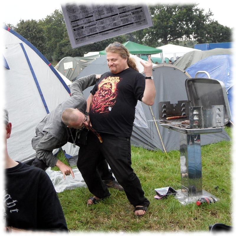 Immer noch betrunkener Mitcamper simuliert eine Fellatio im Stehen mit einer vorgehaltenen Bratwurst.